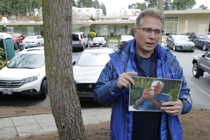In this March file photo, Scott Sedlacek poses while holding a picture of his father, Chuck. Both men battled COVID-19.
