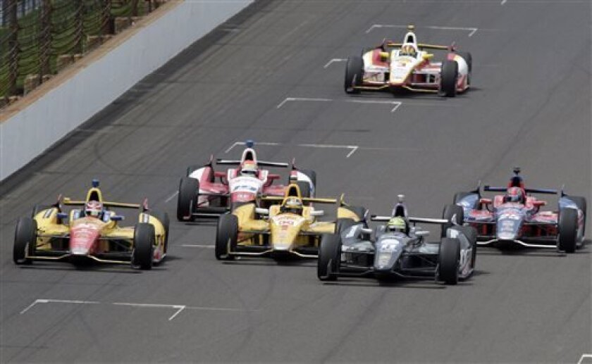 Tony Kanaan, second from right, of Brazil, passes Ryan Hunter-Reay (1) on the 197th lap to takes the lead on his way to winning the Indianapolis 500 auto race at the Indianapolis Motor Speedway in Indianapolis, Sunday, May 26, 2013. Carlos Munoz, of Colombia, (26) finished second, Ray finished thir