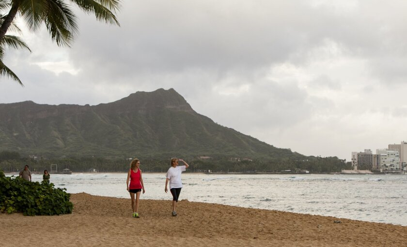 Visitors Sharon Zappa, left, of Florida, and Vicki Stearns, of Chicago, walk along the beach in Waikiki in Honolulu on Friday, Aug, 8, 2014. Iselle came ashore early Friday as a weakened tropical storm, while Hurricane Julio, close behind it, strengthened and is forecasted to pass north of the islands. The two tourists said they were not concerned about the storm. (AP Photo/Marco Garcia)