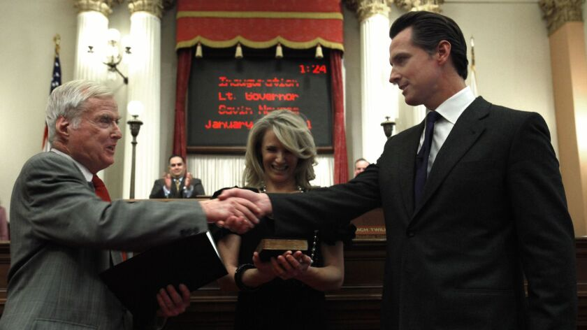 Gavin Newsom, right, shakes hands with his father, William Newsom, a former justice of the state Court of Appeal, who swore his son into office as lieutenant governor in 2011. Gavin Newsom's wife, Jennifer Siebel Newsom is shown in the middle.