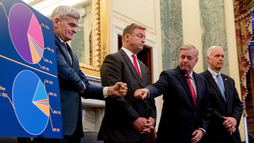 Sen. Bill Cassidy, R-La., left, and Sen. Lindsey Graham, R-S.C., second from right, with Sen. Dean Heller, R-Nev., second from left, and Sen. Ron Johnson, R-Wis., right, fist bump each other during a news conference in Washington on Sept. 13.