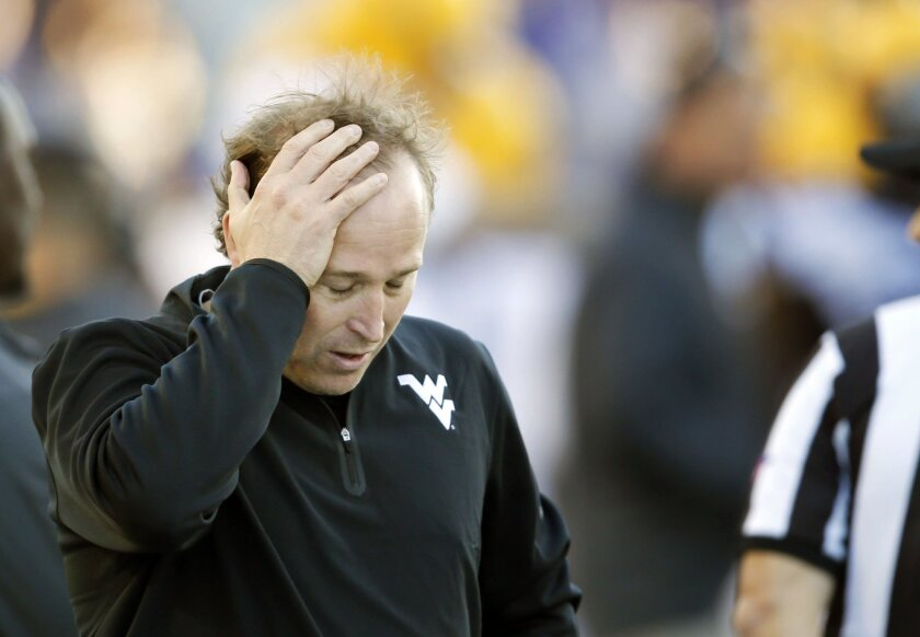 FILE - In this Oct. 26, 2013, file photo, West Virginia coach Dana Holgorsen holds his head during the second half of an NCAA college football game against Kansas State in Manhattan, Kan. Holgorsen needs no reminder about the lack of success he's seen on the field since ushering in West Virginia's move to the Big 12. (AP Photo/Orlin Wagner, File)