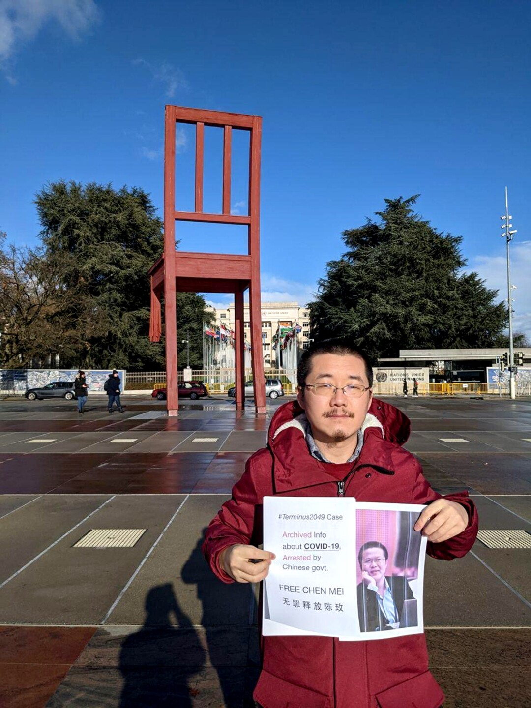 A man standing in front of a red sculpture of a chair holds a printed image of a person and a sign that reads Free Chen Mei
