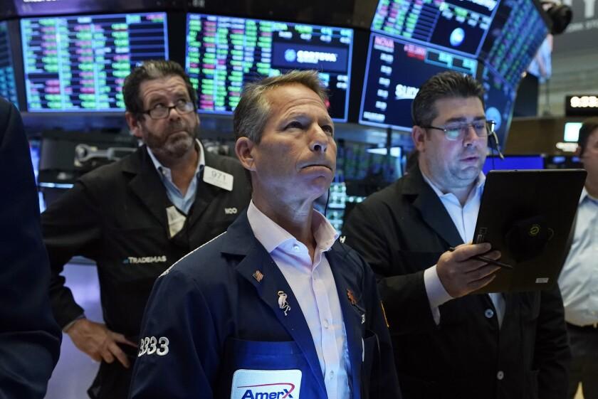 Un trio de operadores trabajando en el piso de la Bolsa de Valores de Nueva York, el martes 21 de septiembre de 2021. (AP Foto/Richard Drew)