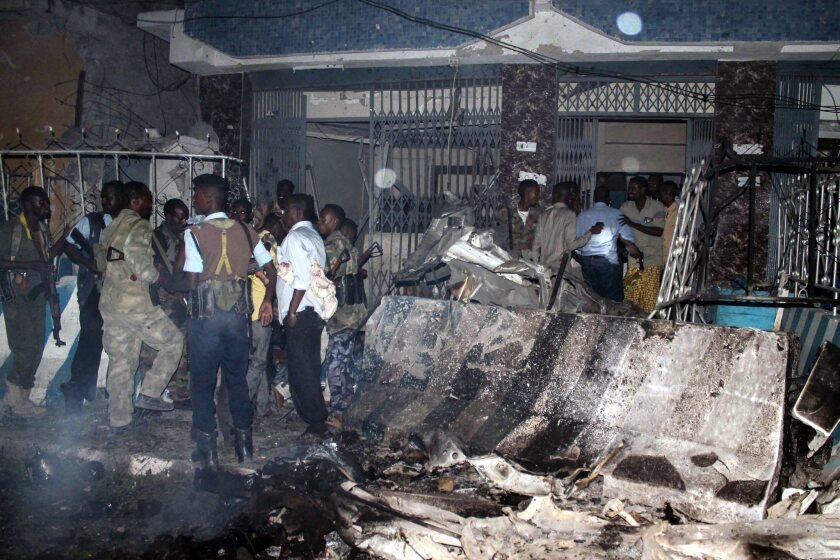 Somali security officers investigate a car bombing in Mogadishu, the capital of Somalia, on July 10, 2015. News reports said at least four people died. Shabab claimed responsibility.