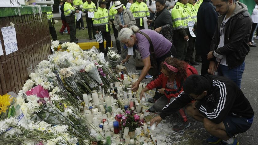 People light candles during a tribute to victims of a car bomb attack at the headquarters of the police academy General Santander in Bogota, Colombia, on Sunday.