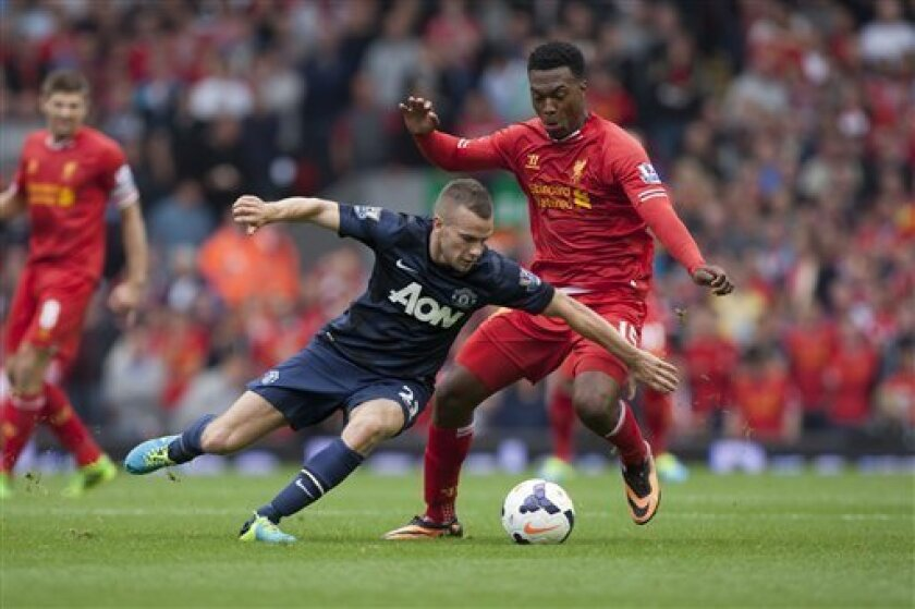 Liverpool's Daniel Sturridge, right, fights for the ball against Manchester United's Tom Cleverley during their English Premier League soccer match at Anfield Stadium, Liverpool, England, Sunday Sept. 1, 2013. (AP Photo/Jon Super)