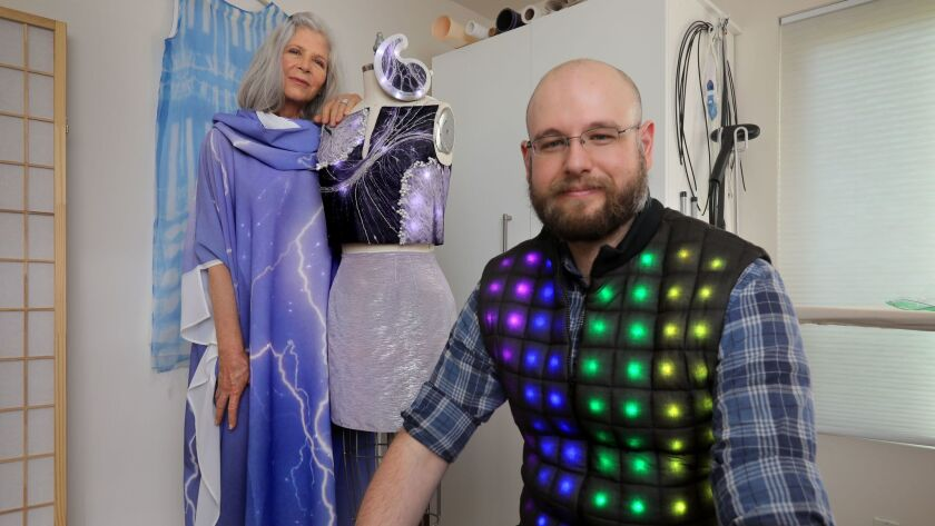 Mother-and-son lighted clothing design team Rachel Merrill and Devon Merrill at her Carmel Valley home and studio. She's wearing their Lightning dress and standing next to their Light Dance project, while he's in their Wearlight vest.