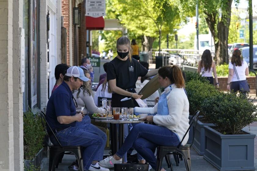 Comensales son asistidos en un café en Franklin Steet, en Chapel Hill, Carolina del Norte