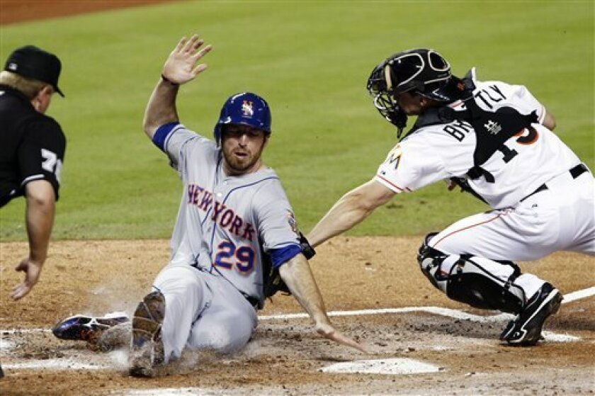 New York Mets' Ike Davis (29) is tagged out at home plate by Miami Marlins catcher Rob Brantly (19) as home plate umpire Mike Muchinski, left, watches the play in the second inning of a baseball game in Miami, Monday, Oct. 1, 2012. (AP Photo/Alan Diaz)