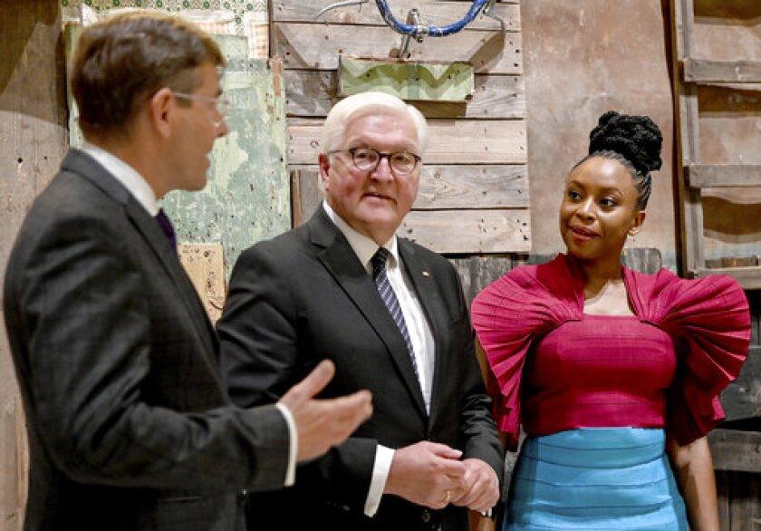 El presidente alemán Frank-Walter Steinmeier, centro, y la escritora nigeriana Chimamanda Ngozi Adichie, derecha, recorren la exhibición guiados por Hartmut Dorgerloh, director general y presidente del directorio de la Fundación Foro Humboldt, en el Palacio Berlín, Berlín, miércoles 22 de septiembre de 2021. (Britta Pedersen/Pool via AP)