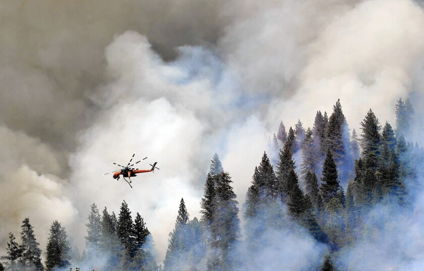 A helicopter flies over Willow Creek Canyon as the Willow fire burns near Bass Lake. A mandatory evacuation was ordered for Cascadel Woods, a hamlet about a mile from the flames.