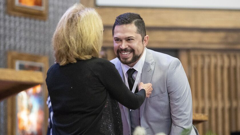 Mary Wickman places a nursing pin on a lanyard over the head of Miguel Rosado during a ceremony Thursday at Vanguard University in Costa Mesa.