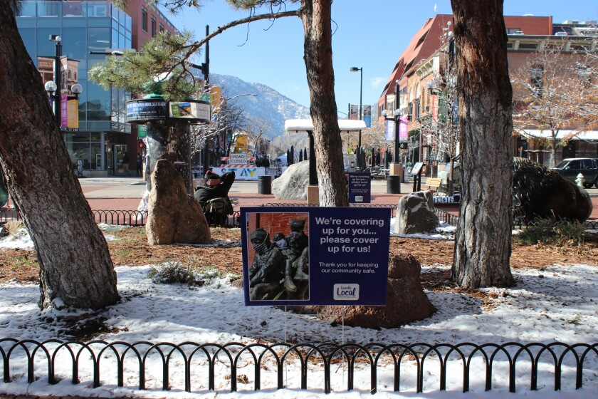 """A sign, amid snow at a small Colorado park, reads """"We're covering up for you ... please cover up for us."""""""