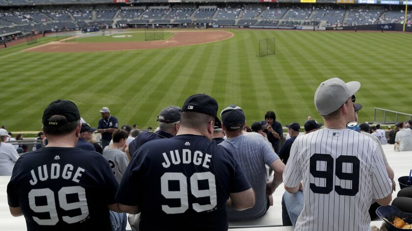 FILE - In this May 4, 2018, file photo, baseball fans wearing New York Yankees' Aaron Judge (99) jer