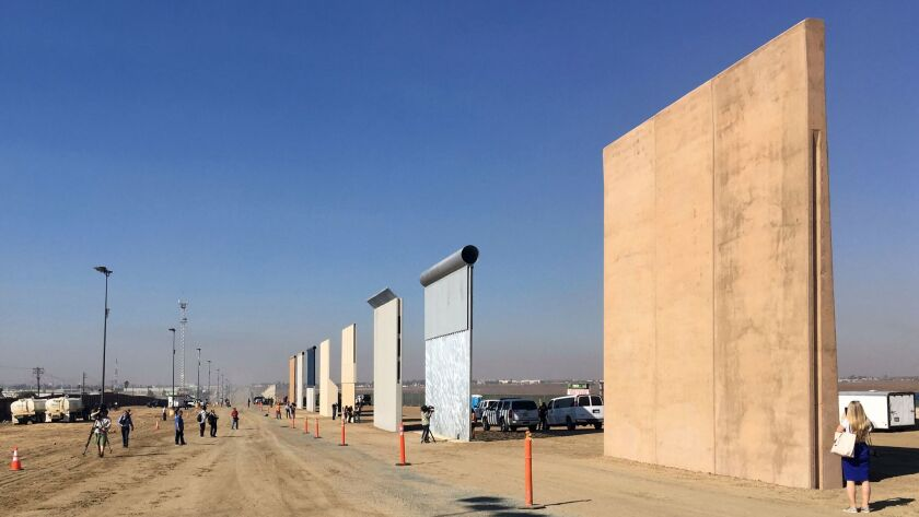 People look at prototypes of a border wall Thursday, Oct. 26, 2017, in San Diego. Contractors have c