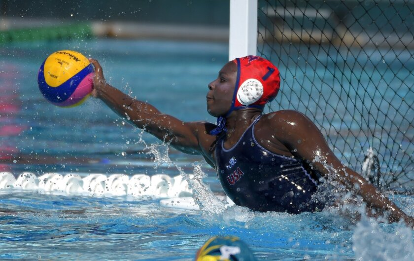 In this May 22, 2016, photo, U.S. goalkeeper Ashleigh Johnson stops a shot during an exhibition water polo match against Australia in Los Angeles. Johnson, a goaltender blessed with jaw-dropping athleticism, is a lock for Rio de Janeiro, putting her on track to become the first black woman to play