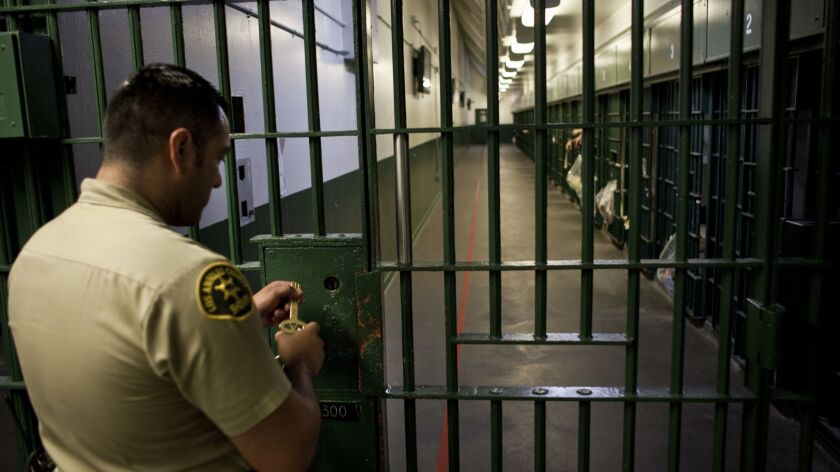 1-A Los Angeles County Sheriff's deputy prepares to unlock a security door at the L.A. County Men's Central Jail.
