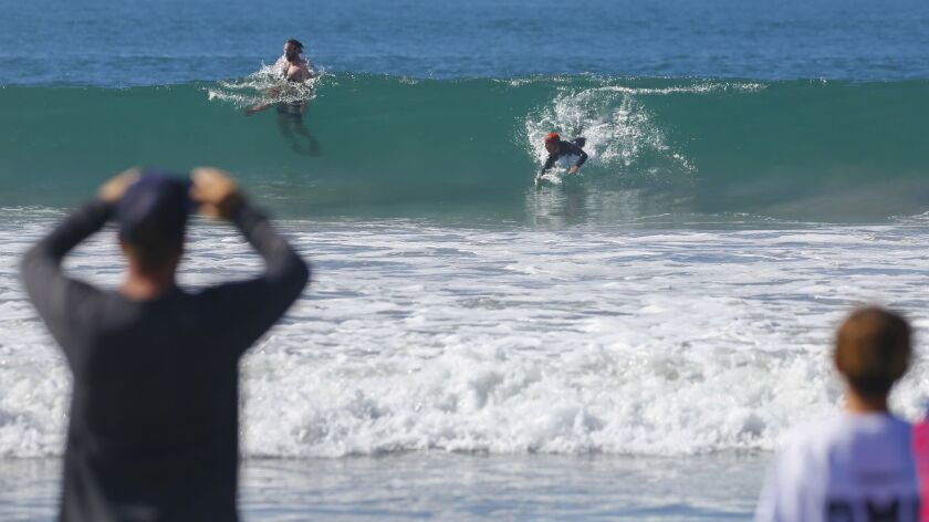 Spectators look on as Hudson Marovush, 14, catches a wave in the URT Womp youth bodysurfing competition.