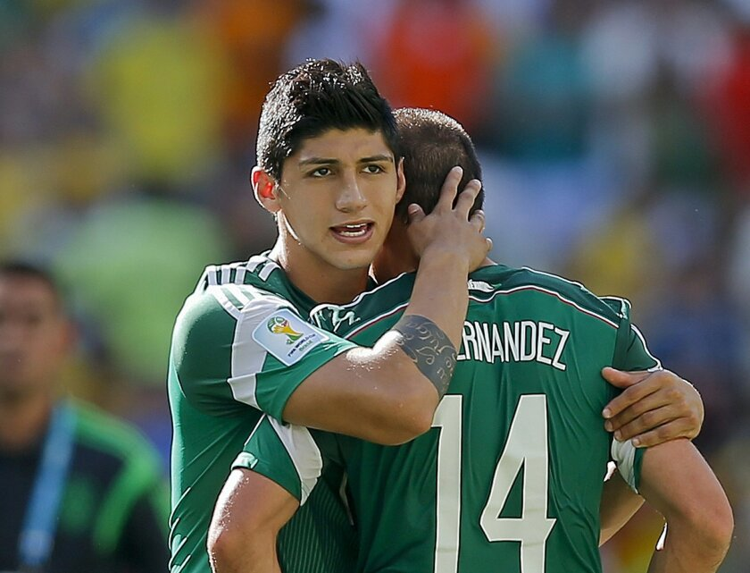 FILE - In a June 29, 2014 file photo, Mexico's Alan Pulido consoles teammate Javier Hernandez (14) after the Netherlands defeated Mexico 2-1 during the World Cup round of 16 soccer match between the Netherlands and Mexico at the Arena Castelao in Fortaleza, Brazil. A state official says that Mexican soccer star Alan Pulido has been kidnapped in the northern border state of Tamaulipas. The official says the 25-year-old player was kidnapped near his hometown of Ciudad Victoria on Sunday after leaving a party. (AP Photo/Eduardo Verdugo, File)
