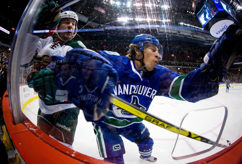 Vancouver Canucks' David Booth, right, misses the check on Minnesota Wild's Keith Ballard and crashes into the glass during the first period of an NHL hockey game Friday, Feb. 28, 2014, in Vancouver, British Columbia. (AP Photo/The Canadian Press, Darryl Dyck)
