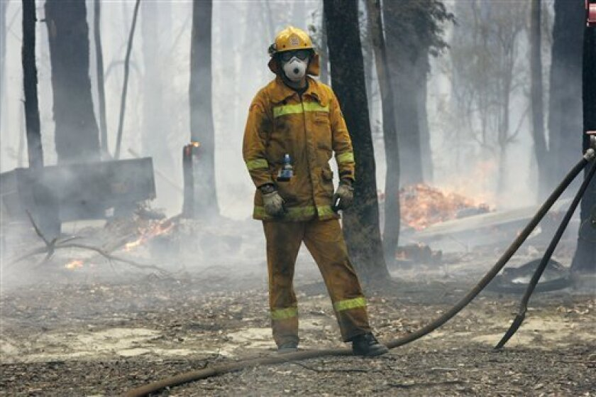 A firefighter stands by to man the pump on his truck at a fire at Chum Creek, near Healseville, north east of Melbourne, Australia Tuesday, Feb. 10, 2009. Officials believe arson may be behind at least some of the more than 400 fires that tore a destructive path across a vast swath of southern Victoria state over the weekend.(AP Photo/Rick Rycroft)