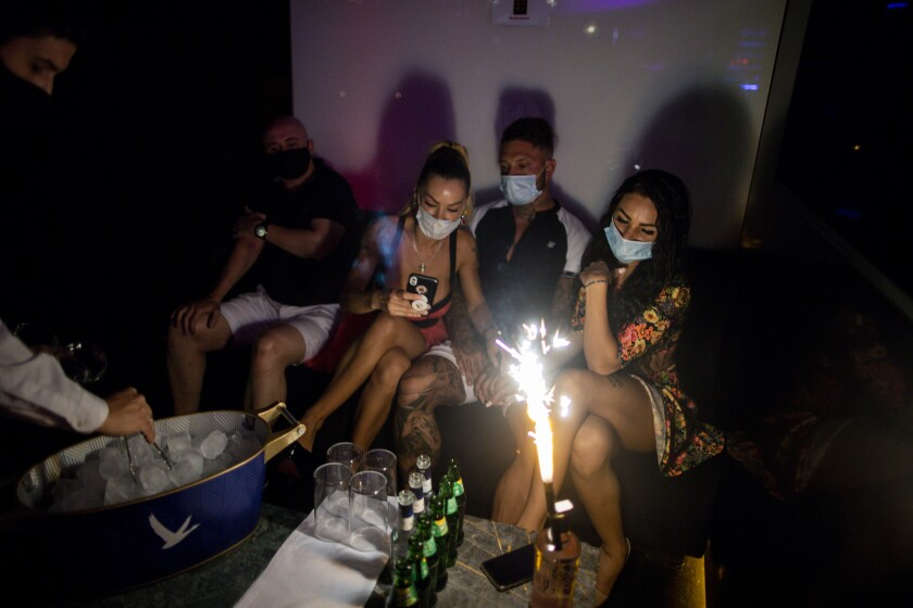 People wearing face masks to prevent the spread of coronavirus gather in a discotheque in Madrid, Spain.