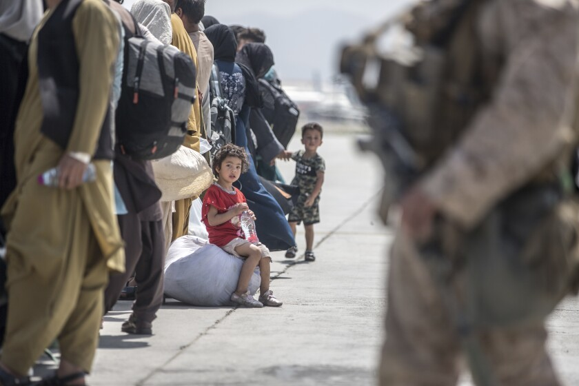 A child waits with her family to board a U.S. Air Force Boeing C-17