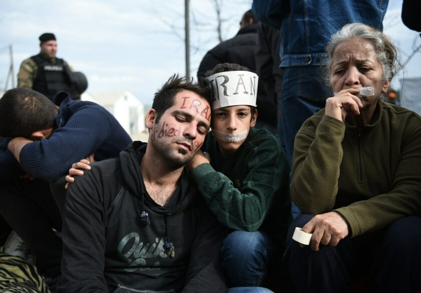 """Exhausted migrants sit in no-man's land demanding to be allowed to pass the Greek-Macedonian border near the northern Greek village of Idomeni, Tuesday, Nov. 24, 2015. Several European countries, including EU members Slovenia and Croatia and non-members Serbia and Macedonia, have declared they will only allow """"war-zone refugees"""" from Afghanistan, Iraq and Syria to transit through their countries on their way to central and northern Europe. (AP Photo/Giannis Papanikos)"""