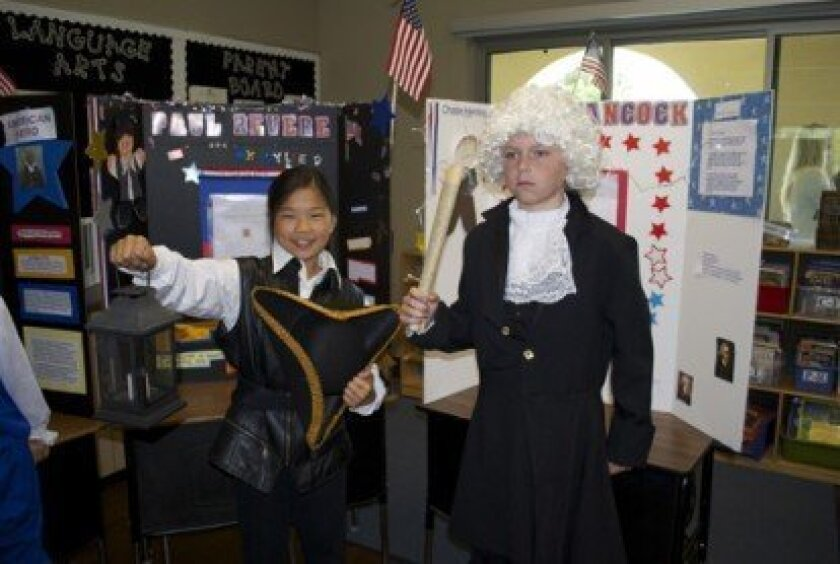 (L-R) Kylie Dypvik and Chase Herring strike their pose as Paul Revere and John Hancock at the 4th Grade Horizon Prep Revolutionary Living History Museum.