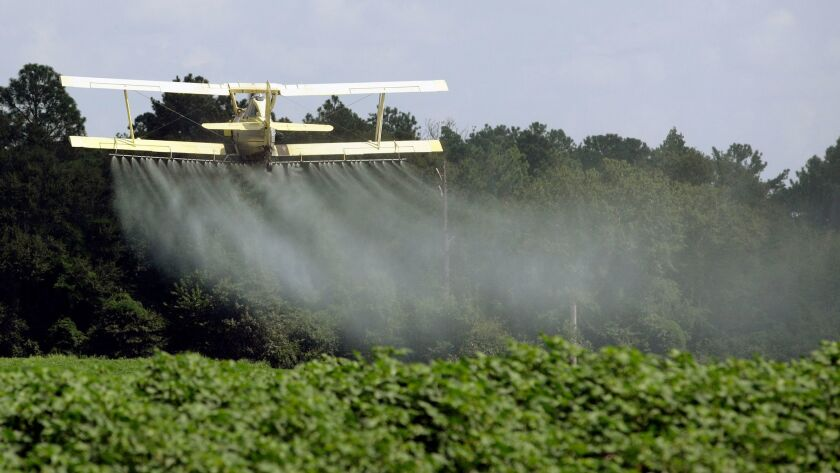 In this photo taken Aug. 4, 2009 file photo, a crop duster sprays a field of crops just outside Head
