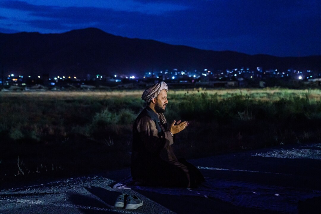A Taliban fighter kneels in the dark while city lights are in the distance behind him