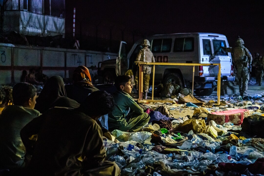 Afghan refugees sit on the ground in a group as British military secure the perimeter outside the Baron Hotel