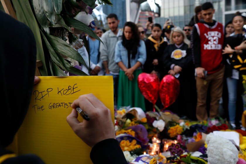 Gilbert Partida writes a note on a memorial board for Kobe Bryant in January in Los Angeles.
