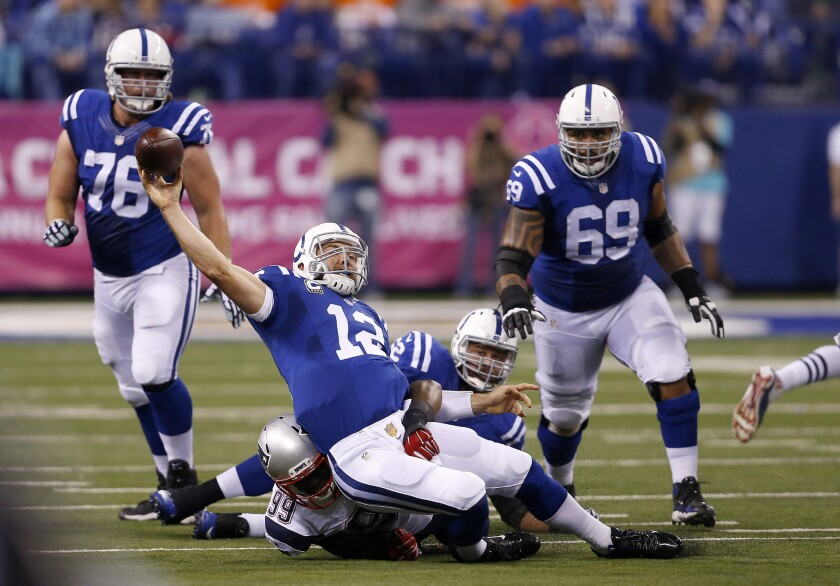 Indianapolis Colts quarterback Andrew Luck (12) is taken down by former New England Patriots defensive tackle Dominique Easley (99) on Oct. 18, 2015.