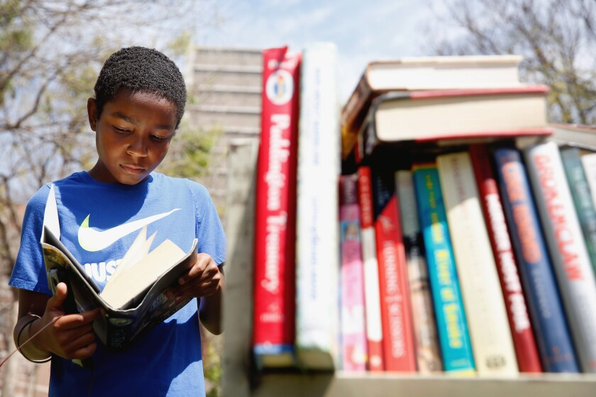 Hasan Paul, 12, peeks into a book for sale during the 2019 Los Angeles Times Festival of Books.