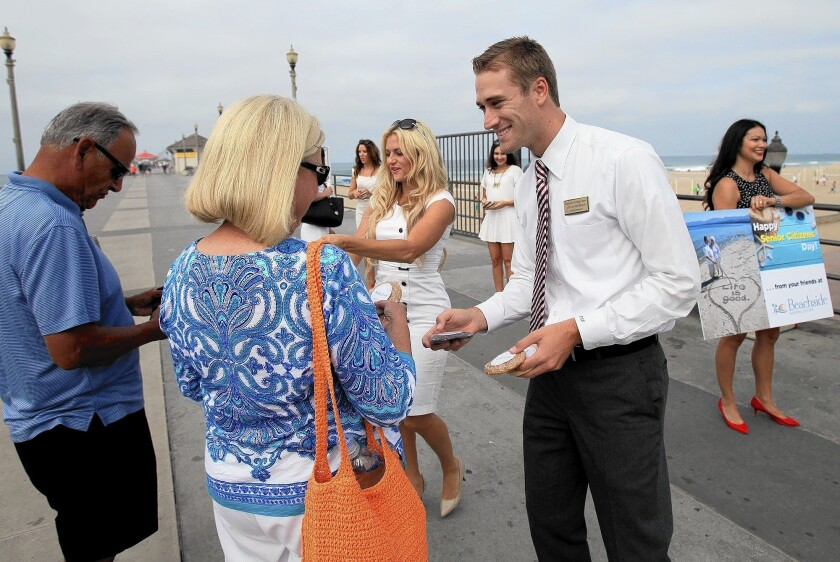 Taylor Florence, administrator for Beachside Nursing Center in Huntington Beach, helps hand out cookies in celebration of National Senior Citizens Day on Aug. 21 at the Huntington Beach Pier.