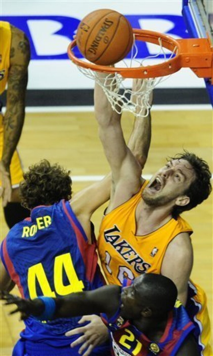 Los Angeles Lakers player Pau Gasol, right, drives for the basket against FC Barcelona's Roger Grimau, left, during the NBA Europe Live 2010 Tour in Barcelona, Spain, Thursday, Oct. 7, 2010. (AP Photo/Manu Fernandez)
