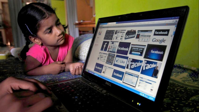 FILE– In this Friday, May 18, 2012, file photo, a child looks at a laptop displaying Facebook logos