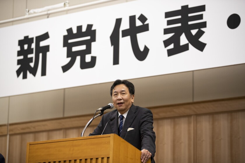 """Yukio Edano, the leader newly elected after two opposition parties' merger, speaks during a news conference in Tokyo on Thursday, Sept. 10, 2020. A 149-member group on Thursday chose Edano, a lawyer-turned politician, as new leader and decided to adopt the Constitutional Democratic Party of Japan, the name of the party he previously headed, as two main opposition parties merged. The word, partly seen at top, read: """" New party leader"""". (AP Photo/Hiro Komae)"""