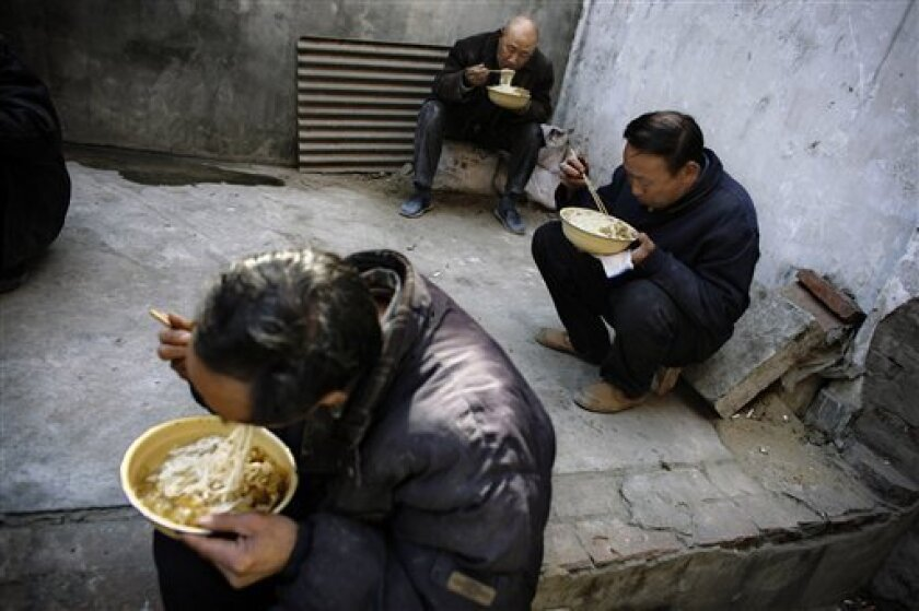 In this March 13, 2008 file photo, workers eat lunch near a construction site in Beijing. An estimated 20 million migrant workers have lost jobs because of the global economic crisis, a government official said Monday, Feb. 2, 2009, giving the government a huge worry as it tries to maintain social stability. (AP Photo/Oded Balilty, File)