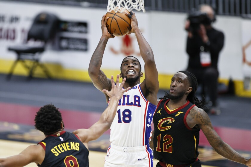 Philadelphia 76ers' Shake Milton (18) goes up for a shot between Cleveland Cavaliers' Taurean Prince (12) and Lamar Stevens (8) during the second half of an NBA basketball game Thursday, April 1, 2021, in Cleveland. (AP Photo/Ron Schwane)