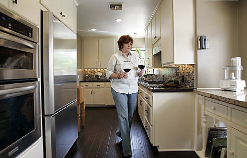 Vicki Reitz walks through the remodeled kitchen. By using the original kitchen's footprint and painting the cabinets, she completed the project for about $18,000.