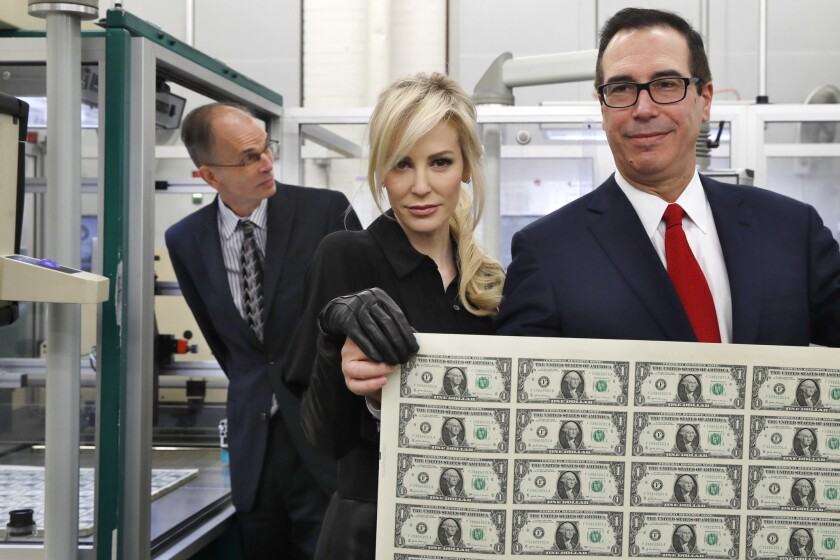 Treasury Secretary Steven Mnuchin, right, and wife, Louise Linton, hold an uncut sheet of $1 dollar notes at the Bureau of Engraving and Printing on Nov. 15, 2017. The new $1 bills, with Mnuchin and U.S. Treasurer Jovita Carranza's signatures, are expected to go into circulation in December.
