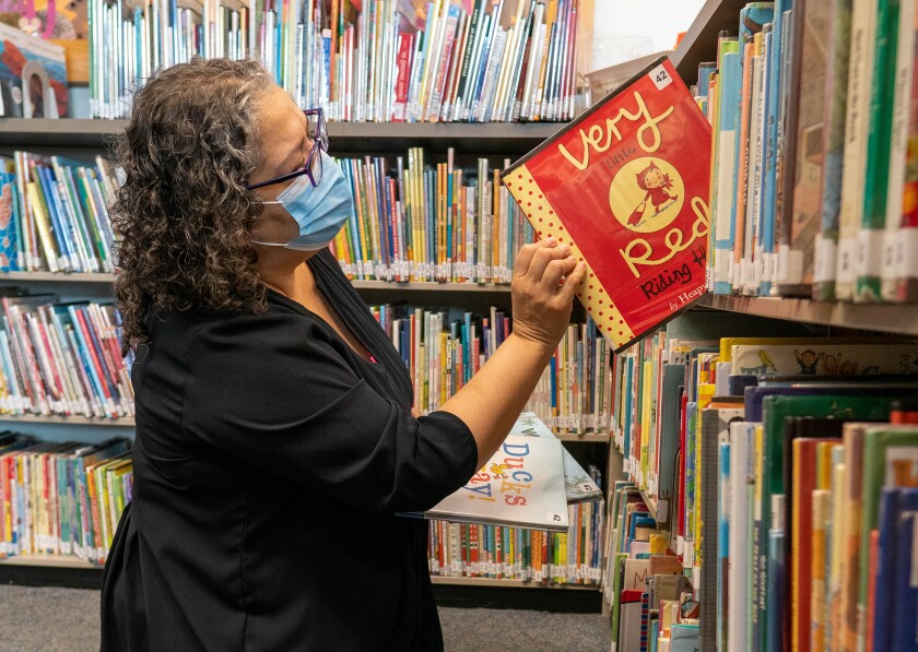 A woman pulls a book off of a shelf at a Los Angeles Public Library branch.