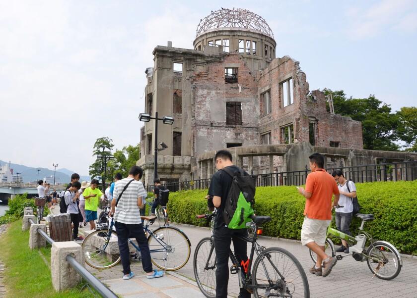 En esta imagen de archivo, tomada el 26 de julio de 2016, un grupo de personas juega a Pokémon Go cerca de la Cúpula de la Bomba Atómica, en el Peace Memorial Park de Hiroshima, Japón. (Kyodo News via AP, archivo)