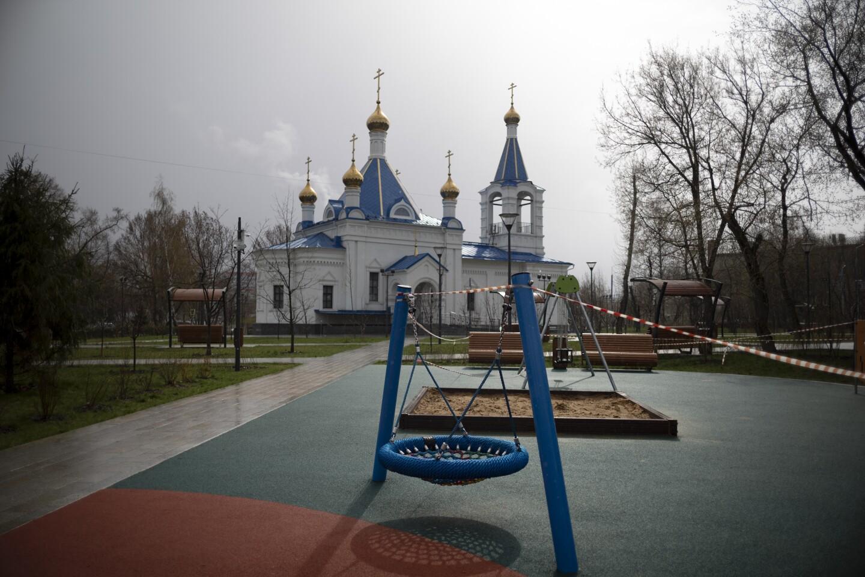 Una cinta acordona un parque infantil vacío en una iglesia ortodoxa, cerrada al culto por la pandemia del coronavirus, en Moscú, Rusia, el 18 de abril de 2020. (AP Foto/Alexander Zemlianichenko)