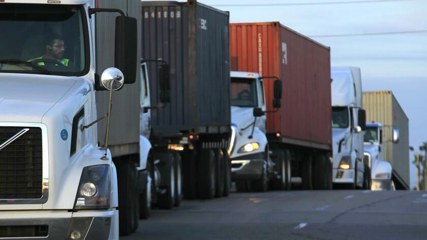 Trucks wait in line to take cargo to a pier in Long Beach in 2014.