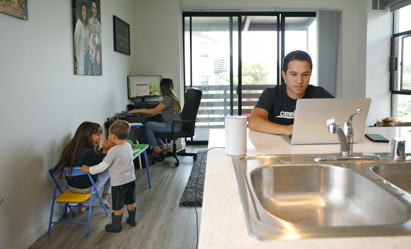 Lucas Fernandez and his wife Deicy work from their La Mesa apartment with their children, Vienna, 7 and Lucas Jr., 2.