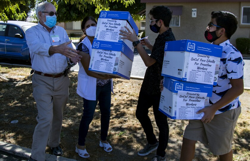 Zubin Carvalho, 14, left and his brother Tenzing, 12, donate boxes of their homemade face shields.